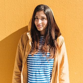 Mulher bonita em pé contra a parede amarela