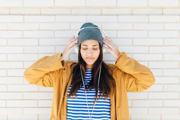 Mulher bonita em pé contra a parede de tijolos brancos usando fones de ouvido