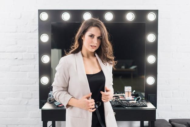 Mulher bonita em pé contra o espelho de maquiagem