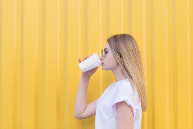 Mulher bonita em pé de perfil contra a parede amarela e tomando café da xícara.