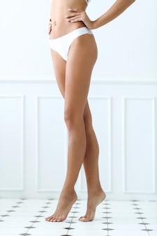 Mulher bonita em pé descalço em um azulejo em um banheiro