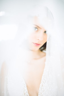 Mulher bonita em pé e olhando na sala com branco no vestido branco longo.