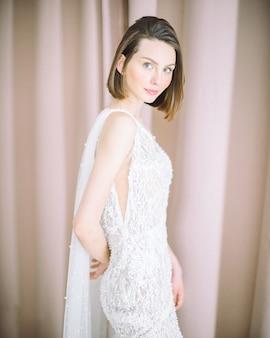 Mulher bonita em pé e olhando na sala com fundo pérola em vestido longo branco.