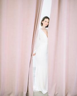 Mulher bonita em pé e olhando no quarto pérola vestido longo branco.