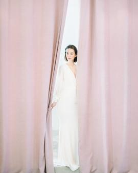 Mulher bonita em pé e pensando em vestido longo branco na sala de pérolas.