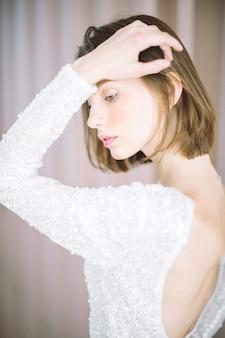 Mulher bonita em pé e pensando na sala com pérolas na camisa branca.