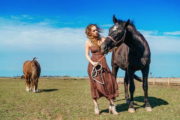 Mulher bonita em pé em um campo com um cavalo
