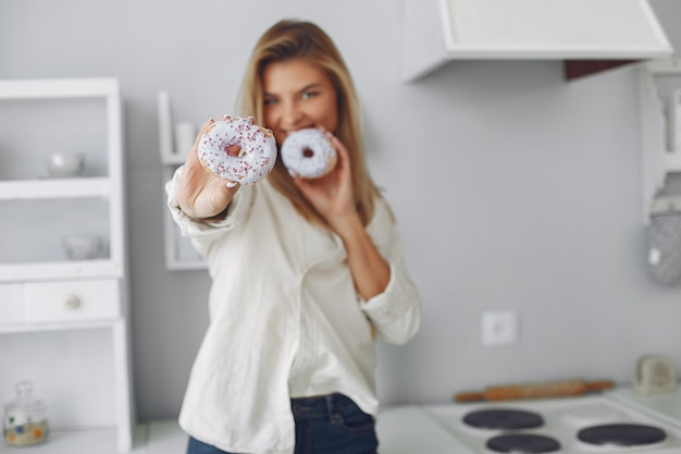Mulher bonita em pé em uma cozinha com rosquinha