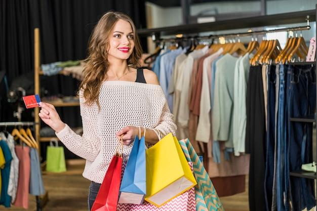 Mulher bonita em pé na boutique segurando sacolas de compras e cartão de crédito na mão