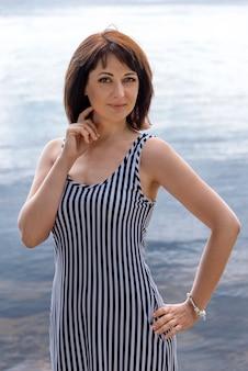 Mulher bonita em pé na margem de um lago que desfruta de seu passeio