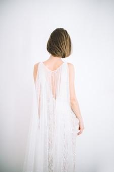 Mulher bonita em pé na sala com vestido branco longo branco vista traseira.