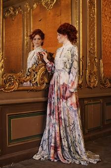 Mulher bonita em pé na sala do palácio com espelho.