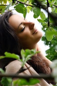 Mulher bonita em pé pela árvore florescendo no parque verde