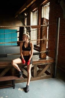 Mulher bonita em pé pelo ringue de boxe