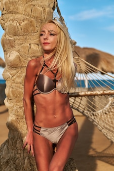Mulher bonita em pé perto de uma palmeira na praia