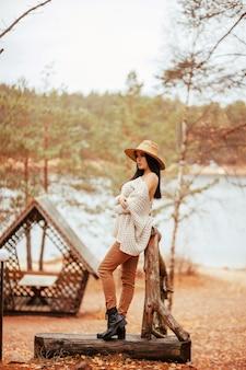 Mulher bonita em pé perto do lago, caramanchão de madeira e escada