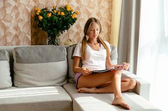 Mulher bonita em revista de leitura de roupa em casa em casa no sofá