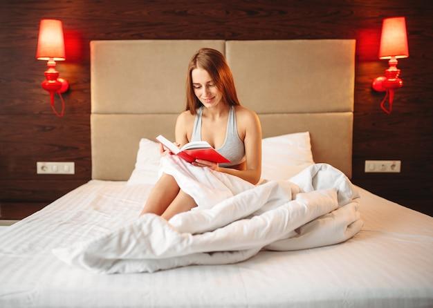 Mulher bonita em roupa interior lê o livro na cama. menina acorda de manhã no quarto