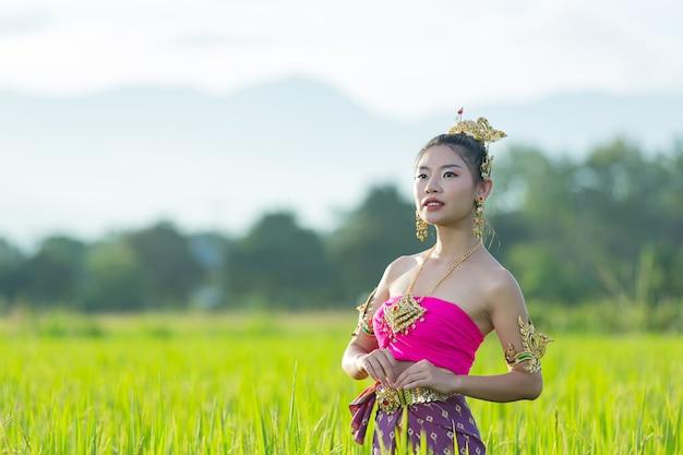 Mulher bonita em roupa tradicional tailandesa sorrindo e em pé no templo