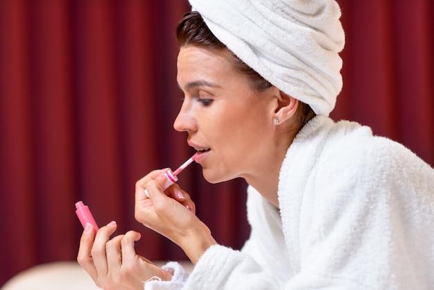 Mulher bonita em roupão com uma toalha na cabeça aplicando batom
