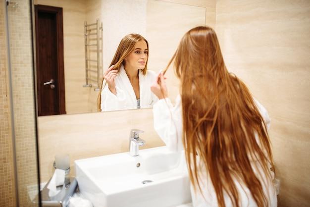 Mulher bonita em roupão de banho contra espelho no banheiro, higiene matinal, beleza e cuidados com os cabelos