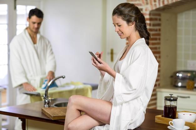 Mulher bonita em roupão de banho sentado na bancada da cozinha e digitando uma mensagem de texto no smartphone enquanto homem passando roupa atrás dela
