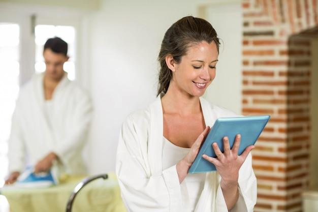 Mulher bonita em roupão sentado na bancada da cozinha e usando tablet digital enquanto homem passando roupa atrás dela