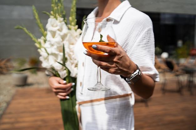 Mulher bonita em roupas brancas. fotografia de moda. modelo posando com flores e cocktail laranja em fundo de madeira.