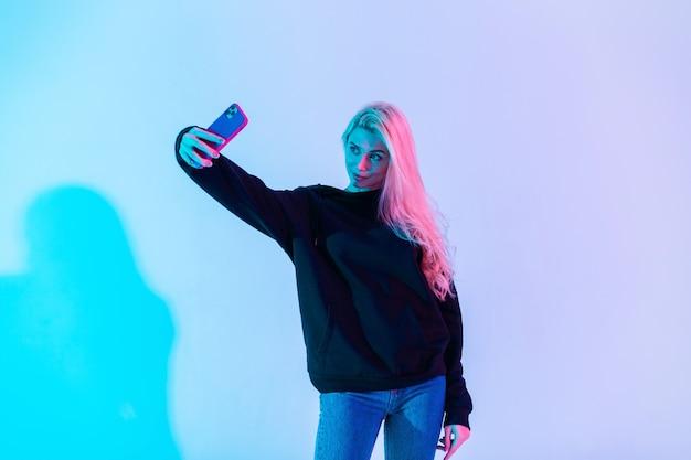 Mulher bonita em roupas casuais da moda, moletom e jeans faz selfie no telefone no estúdio contra fundo de luz rosa neon