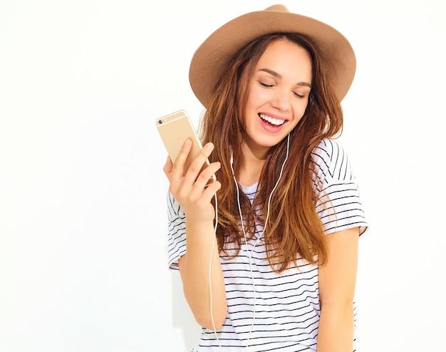 Mulher bonita em roupas de verão casual hipster sem maquiagem no chapéu marrom, ouvindo música no telefone com fones de ouvido isolados no branco