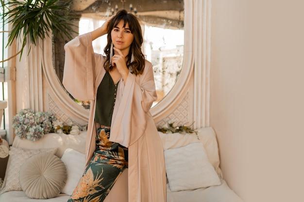 Mulher bonita em roupas femininas elegantes posando em um interior boêmio elegante.