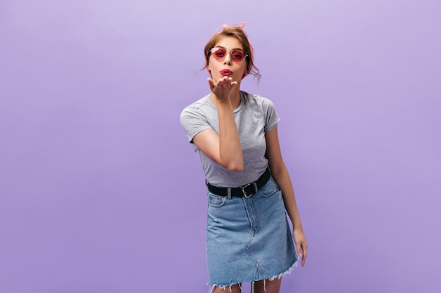 Mulher bonita em saia jeans sopra beijo. linda linda garota de óculos de sol rosa e bandana posando em pano de fundo isolado.