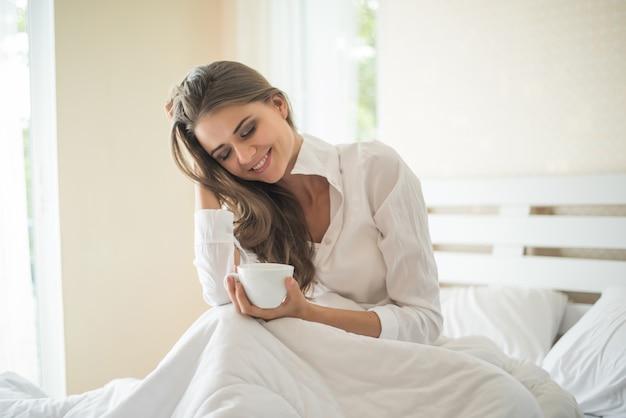 Mulher bonita em seu quarto tomando café da manhã