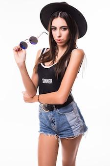 Mulher bonita em shorts de camiseta e óculos escuros posando.