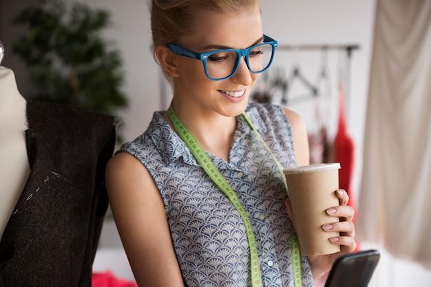 Mulher bonita em sua oficina com telefone celular