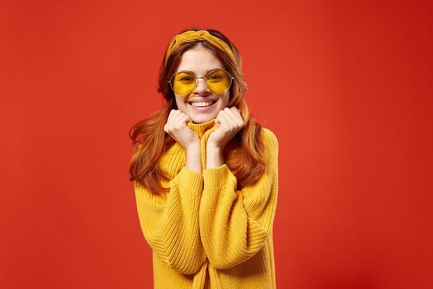 Mulher bonita em suéter amarelo óculos moda emoções fundo vermelho