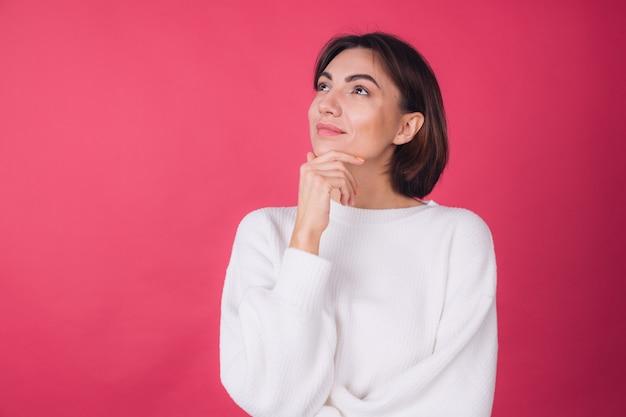 Mulher bonita em suéter branco casual na parede vermelha