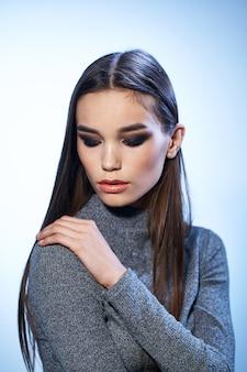 Mulher bonita em suéter cinza maquiagem brilhante encanto de cabelo comprido isolado