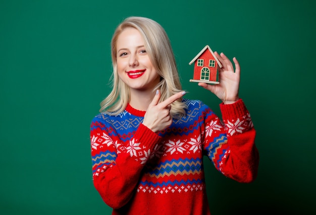 Mulher bonita em suéter de natal com casa de brinquedo