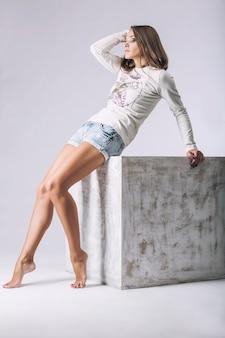 Mulher bonita em suéter e shorts jeans. modelo com roupas da moda com maquiagem em uma superfície leve