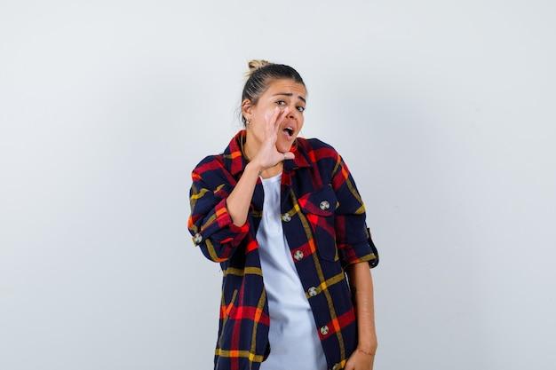 Mulher bonita em t-shirt branca, camisa bochecha com a mão perto da boca para ligar para alguém e olhando com foco, vista frontal.