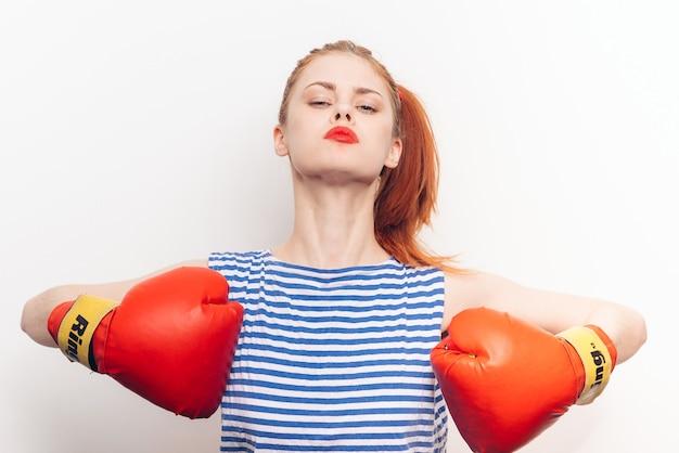 Mulher bonita em t-shirt listrada luvas de boxe treino luz de fundo