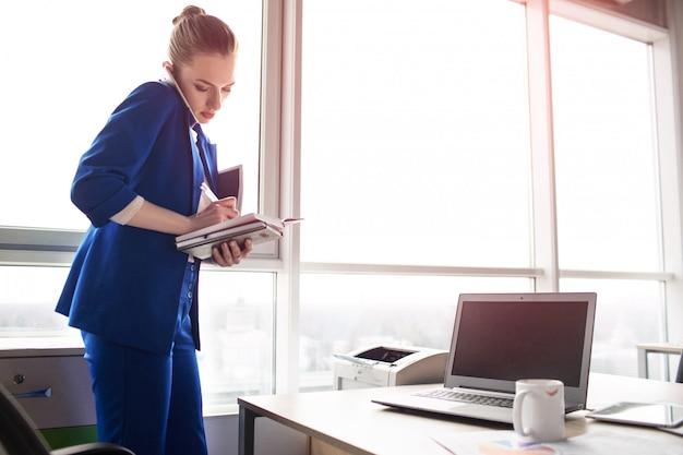 Mulher bonita em traje azul está de pé em seu escritório e falando ao telefone