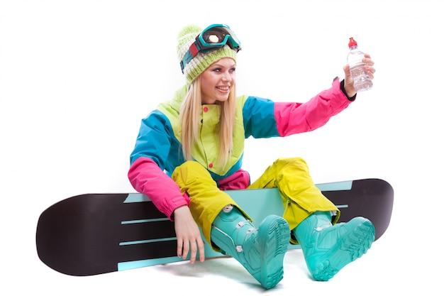 Mulher bonita em traje de esqui com garrafa de água sente-se no snowboard