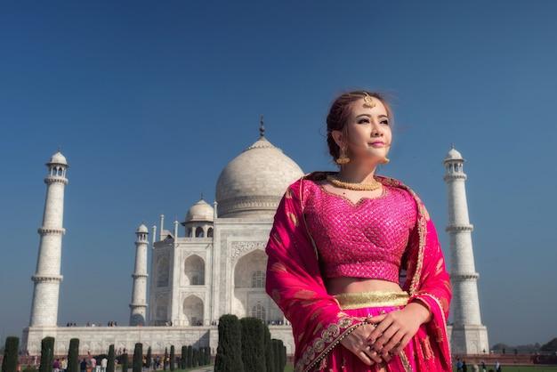 Mulher bonita em traje tradicional, mulher asiática usando cultura de identidade de vestido típico saree / sari da índia. taj mahal scenic a opinião da manhã do monumento de taj mahal em agra, índia.