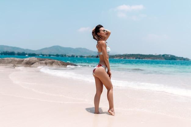 Mulher bonita em trajes de banho coloridos com cabelo comprido, posando na praia de areia branca