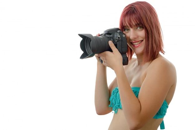 Mulher bonita em trajes de banho segurando a câmera fotográfica digital