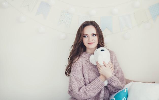 Mulher bonita em um agasalho quente em um quarto de natal decorado
