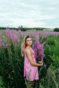 Mulher bonita em um campo de flores cor de rosa.