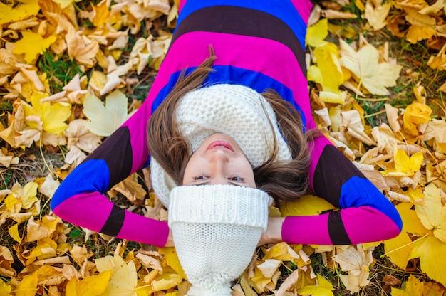 Mulher bonita em um chapéu de malha no parque do outono